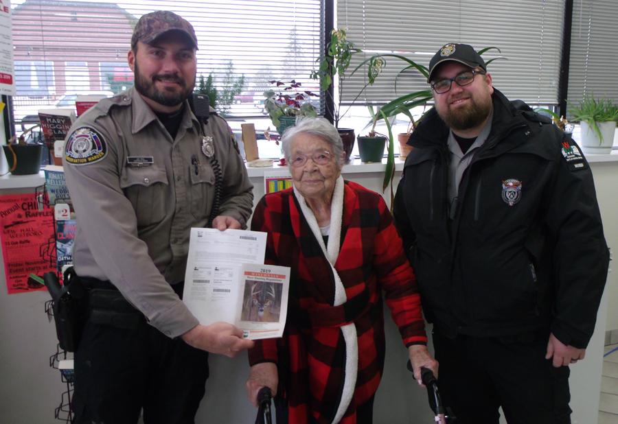 Florence Teeters poses with DNR Wardens after buying her first gun deer license.